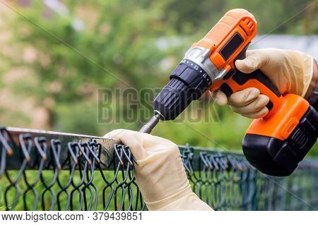 Fastening The Metal Mesh Of The Chain-link With A Drill-screwdriver With An Electric Battery On The