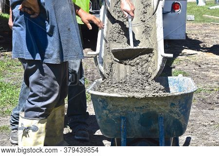 Wet Mud (concrete) Is Being Pushed Down A Chute From A Ready-mix Truck Into A Wheelbarrow.