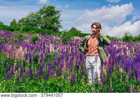 Tall Handsome Man Standing On Lupine Flowers Field