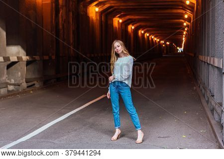 Young Woman Standing In A Tunnel With Lights
