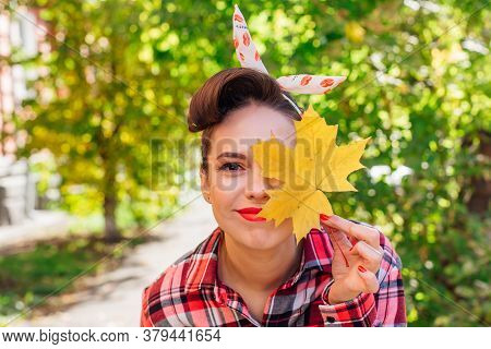 Beautiful Woman With Make Up And Hair In Pin Up Style Standing On The Street, Holding Yellow Maple L