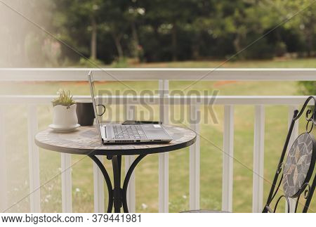Laptop And Coffee On Table In Balcony Garden Green Trees Background On Vacation.