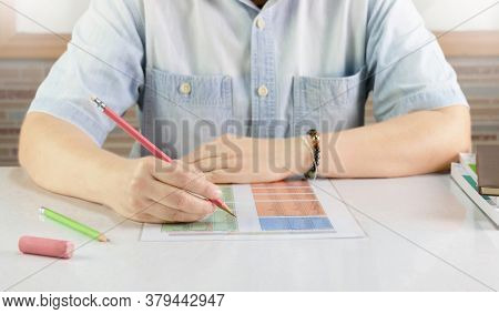 Hand Holding Pencil Over Blurred English Sheet On Desk In Classroom
