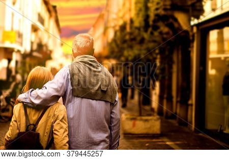 Old dreamy couple carefree walking along the streets of the old city