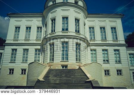 Facade Of Luxury Estate With Stairs. From Below Exterior Of Luxury Mansion With Staircase And Many W