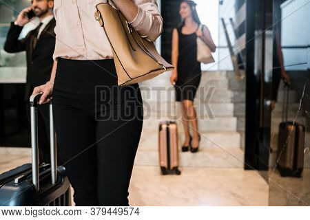 Portrait Of Business People Arriving At Hotel And Walking Through Lobby With Their Luggage. Travel A