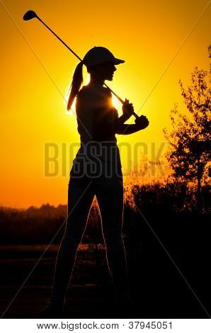 woman golf player tee off during sunset silhouetted