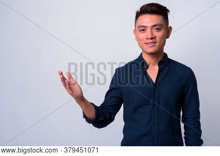 Portrait Of Happy Young Asian Businessman Showing Something
