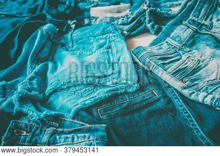 Jeans fast fashion textile industry tons of pairs of pants produced every year going to waste. Closeup of many different denim fabrics of blue indigo dye.