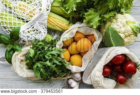 Fresh Fruits And Vegetables In Eco Cotton Bags On Table In The Kitchen. Corn,  Apricots, Tomatoes, R