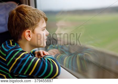 Adorable Kid Boy Traveling By Train. Happy Smiling Child Looking Out Of The Window During Train Movi