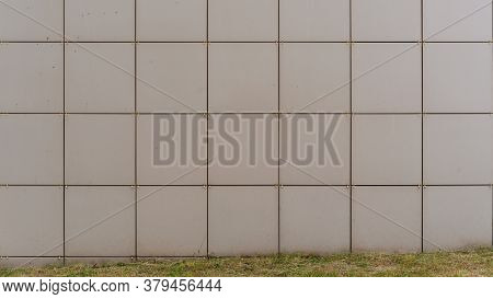 White Decorative Tiles On Local City Building Wall Near Green Grass On Flowerbed Under Bright Summer