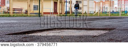 Grey Asphalt Playground With Square Pit Against Distant Alone Boy And Colourful Fence And Buildings