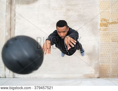 Athletic Man Doing Wall Ball Exercise.