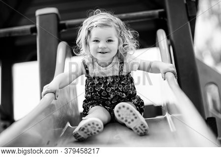 Cute Toddler Girl Playing On Slide On Outdoor Playground. Beautiful Baby In Colorful Shorts Trousers