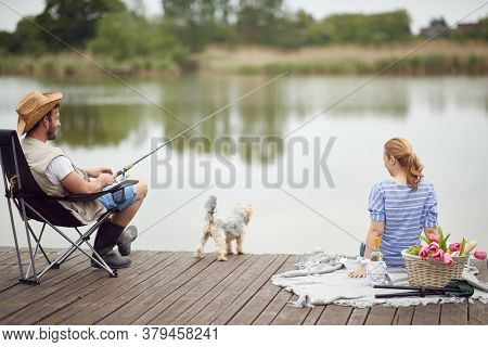 Spouses enjoy fishing and a picnic with their dog on a beautiful day