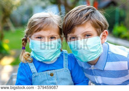 Two Kids, Little Toddler Girl And School Boy In Medical Mask As Protection Against Pandemic Coronavi
