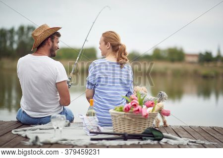 Happy spouses enjoy fishing and a picnic with their dog on a beautiful weather
