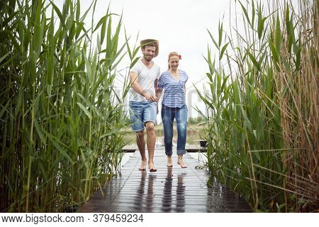 Spouses barefoot walking on a wet dock of the lake