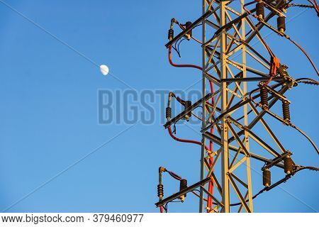 Electricity Transmission Pylons, Power Lines High Voltage Towers Against Blue Sky With Moon.