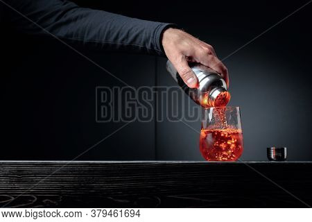 Bartender Pouring Cocktail Into Glass At Bar Counter. Alcoholic Drink Pouring From A Shaker Into A F