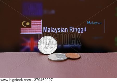 Twenty Cents Coin Of Malaysia Ringgit Money And The Coins On Brown Floor With Digital Board Of Curre