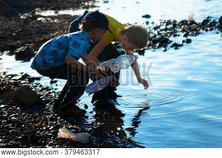 Norilsk, Russia - July, 20, 2017: Two Boys Collect Water In Palstic Bottles From A Polluted Lake. Th
