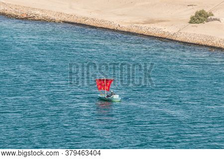 Ismailia, Egypt - November 14, 2019: Fishermen In A Wooden Boat Under A Red Sail Along The Suez Cana