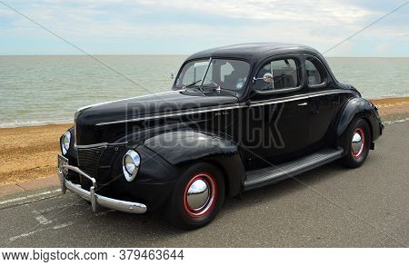 Felixdtowe, Suffolk, England - May 01, 2016: Classic Black Ford Deluxe Coupe Parked On Seafront Prom
