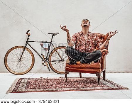 Stylish Tattooed Gangster Sits On A Armchair In A Lotus Pose, Looks Very Expressive And Freakly