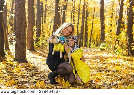 Mother And Daughter With A Dog Jack Russell Terrier. Friendship And Pet Concept. Small Dog Walking I