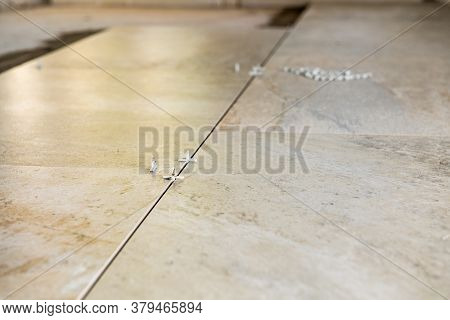 Multiple Tile Spacers In Place On Freshly Installed New Luxury Tiles On The Floor - Reconstruction R