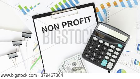 Non Profit. Text On White Paper On Black Envelope Over The Financial Graphics And The Calculator Vie