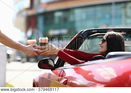 Courier Hands Over Coffee To Woman In Car. Fast Food And Beverage Delivery Concept