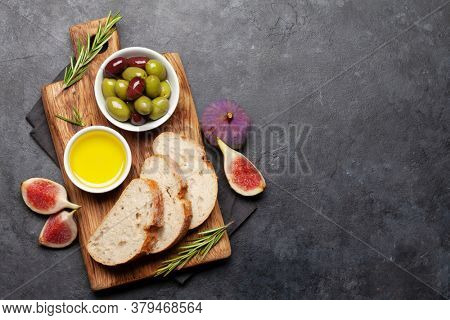 Ripe olives, olive oil, figs and ciabatta bread. Top view flat lay with copy space