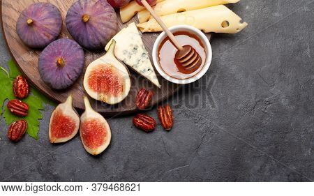 Antipasto plate with cheese, figs and grapes. Appetizer board. Top view flat lay with copy space