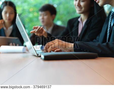 Side View Of Office Workers Consulting On Their Work With Laptop In Meeting Room