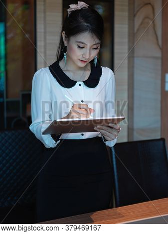 Portrait Of Businesswoman Working On Digital Tablet While Standing In Meeting Room