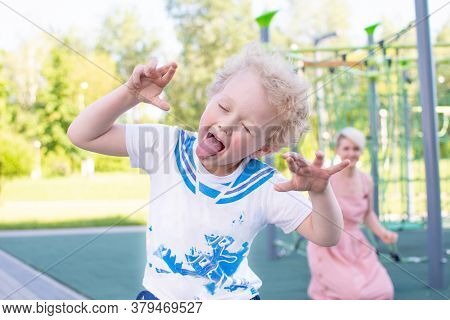 Curly-haired Boy Shows His Tongue, Teases. Playing With Her Mother On The Playground