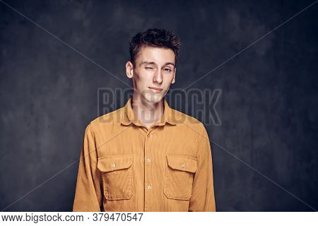 Winking Young Caucasian Man On Grey Dark Background With Copy Space