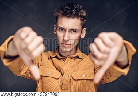 Young Caucasian Man Show Thumbs Down On Grey Dark Background With Copy Space