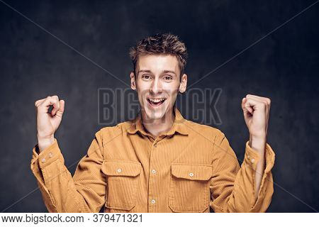 Young Caucasian Man With Success Gesture On Grey Dark Background With Copy Space