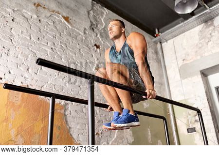 fitness, sport, bodybuilding and people concept - young man doing abdominal exercise on parallel bars in gym