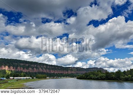 View Of Long Cliff In Shamanka Village In Russia Wih Blue Sky And Clouds Background Near River