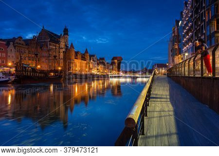 Gdansk, Poland - August 2, 2020: Amazing architecture of Gdansk old town at night with a new footbridge over the Motlawa River. Poland