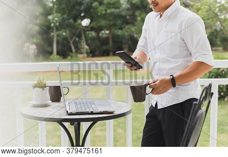 Businessman Checking Mobile Phone Standing In Balcony With Laptop On Table