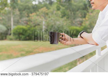 Man Relaxjng Hand Holding Coffee Mug While Standing On Balcony