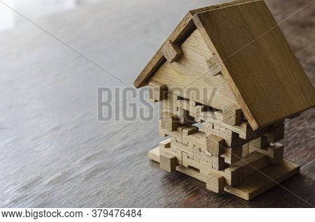 Wooden Toy House On A Wooden Table. Small House Made Of Oak Puzzles. Side View At An Angle. Selectiv
