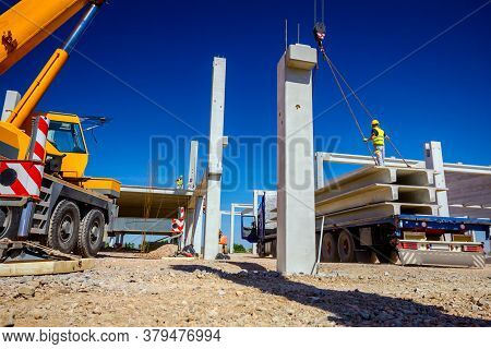 Trailer Truck Is At Unloading Cargo, Concrete Beam For Assembling Concrete Edifice, Building Site.