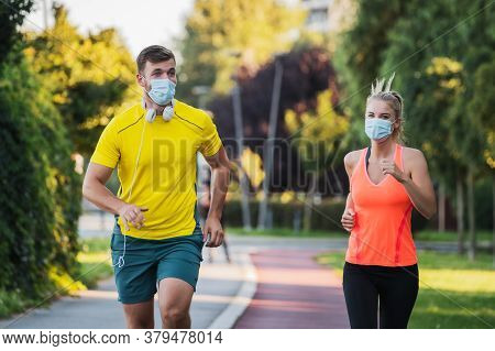 Young Couple Is Jogging With Protective Masks. Covid-19 Responsible Behavior.